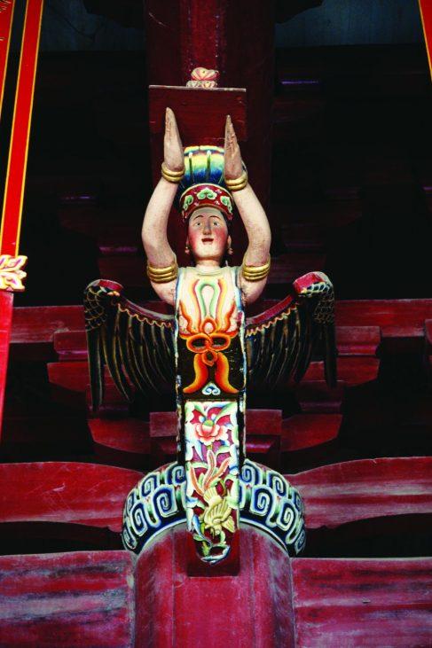 """大殿内石柱和桁梁接合处刻有的24尊""""飞天乐伎"""",不仅集结各宗教造型而塑,也起着承载大殿屋顶重量的功能。摄影:马耀俊"""